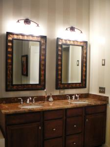 Designer Robin LaMonte's well-chosen bronze mirrors complement the neutral tones of this traditional bathroom.