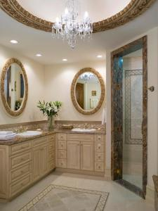 Large, oval mirrors soften the sharp edges of a catty-corner vanity in this bathroom designed by Lori Dennis.