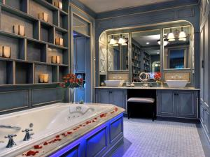 A shabby-chic bathroom is turned into a glamorous retreat with the addition of a large vanity with overhead lights.